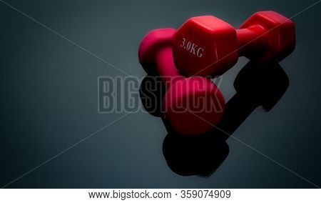 Red And Dark Pink Dumbbells Isolated On Black Background. 2, 3 Kg Dumbbells. Weight Training Equipme