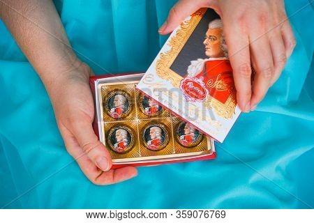 Tambov, Russian Federation - February 14, 2020 Woman Opening Box Of Mozart Candies.