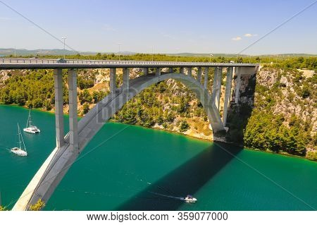 Automobile Long High Arched Bridge Over The Krka River In Croatia Near Sibenik. Picturesque Croatian