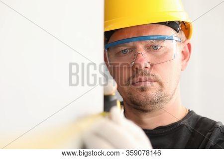 Repairman In Helmet And Mask, Measures Tape Measure. Taking Measurements Using Retractable Tape. Pre