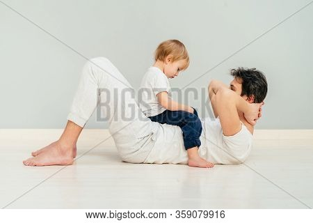 Strong Purposeful Father Babysitting A Child And Trying
