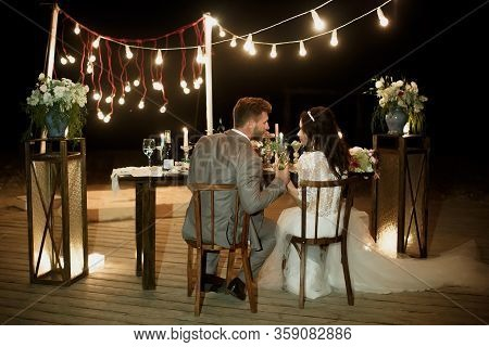 The Night Wedding Ceremony. The Bride And Groom Are Sitting At The Festive Table. Banquet.