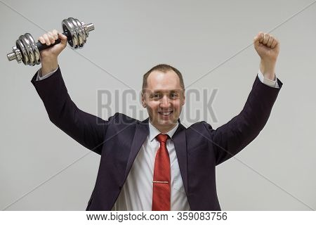 Portrait Of Confident Businessman Lifting Dumbbell Over Light Background