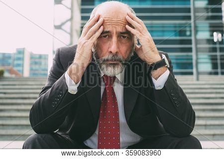 Ruined Businessman Sitting On Steps And Looking At Camera. Front View Of Stressed Mature Businessman