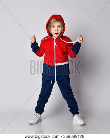 Frolic Excited Surprised Blond Kid Boy In Blue And Red Sportswear Hoodie And Pants Stands With His C
