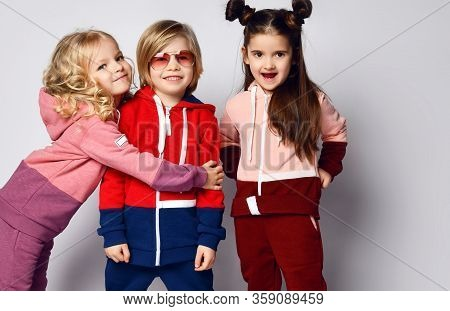 Portrait Of Three Frolic Active Kids In Sportswear. Curly Hair Blonde Girl, Her Brother Blond Boy An