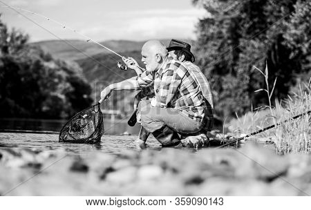 Beautiful Evening Riverside. Men Riverside Catching Fish. Teaching Fishing. Transferring Knowledge.