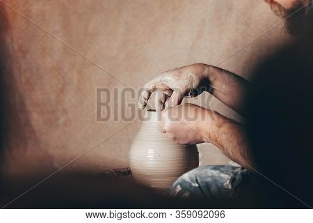 Man Forms Clay Jar On Potter's Wheel. Potter In The Process Of Work Side View