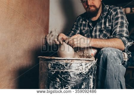 Pottery Master Works On Pottery Wheel In Workshop