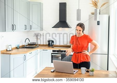Video Conference, Video Meeting. A Young Woman Works From Home, She Uses A Headset For Online Commun
