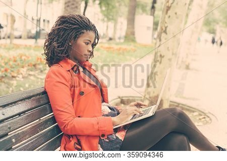 Focused Woman Using Laptop Computer In Park. Side View Of Serious Young African American Woman Using