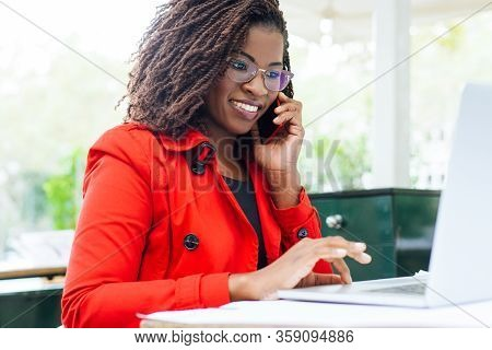 Cheerful Woman Using Laptop And Smartphone. Attractive Young Businesswoman Talking By Cell Phone And
