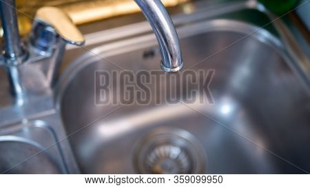Male Hand With A Glass Under The Tap. Glass In Male Hand Is Filled With Clean Transparent Water Unde