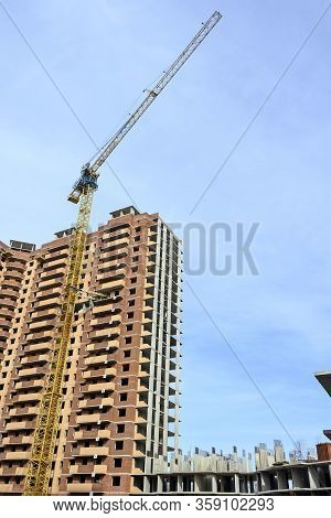 Yellow Tall Tower Construction Crane On A Background Of Blue Sunny Sky And A High-rise Brick House.