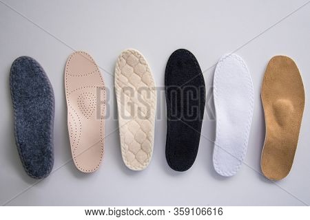 Studio Photo Of Orthopedic Insoles. A Variety Of Orthopedic Insoles Are Laid Out In A Row. Different
