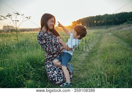 Stilish Mother And Handsome Son Having Fun On The Nature. Happy Family Concept. Beauty Nature Scene