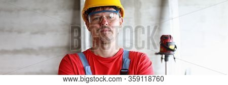 Builder In Helmet Crossed His Arms Over His Chest. Main Stages In Work With Repair Or Construction N