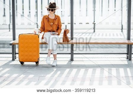 Young Female Traveler Sitting With A Suitcase At The Transport Stop, Waiting For The Tram Or Bus. Di