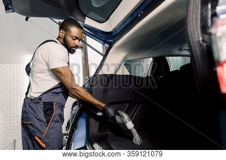 African Male Worker Wearing White T-shirt And Gray Overalls, Vacuuming Car Interior, Trunk With Wet