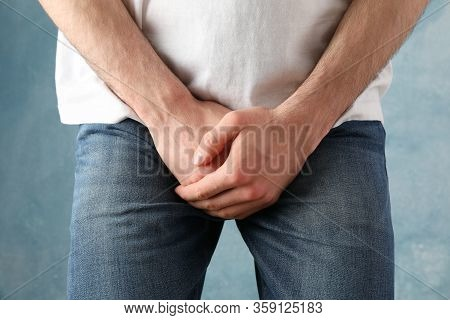 Man Holds His Crotch On Blue Background, Close Up
