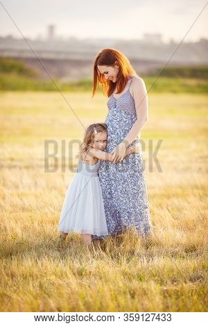 Mom With Long Dark Hair With A Little Fair Haired Daughter In Grey Dress In Summer Field Hugging