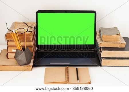 Home Office: Open Textbook, Notebook, Green Screen Laptop Computer, Stack Of Old Books Retro Educati