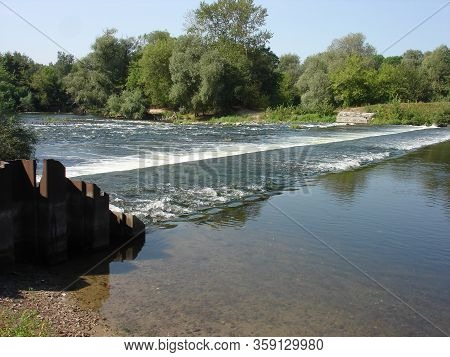 A Wide River On A Summer Morning. There Is An Old Concrete Retaining Dam On The River. The Dam Forms