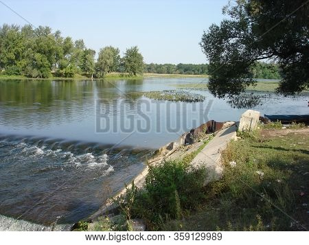 A Wide River On A Summer Morning. The Surface Of The River Was Overgrown With Water Vegetation. Ther