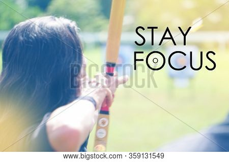 Word Stay Focus over blur background of Archery with a bow in the foreground during an archery compe