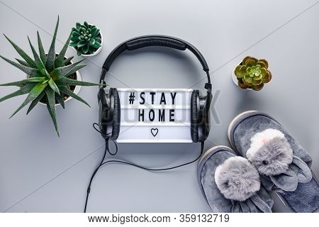 Light Box In Headphones With Text Stay Home, Slippers On Grey Background. Healthcare And Medical Con