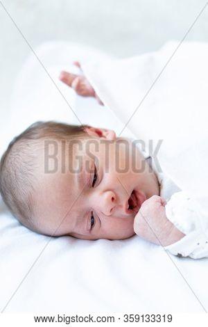 Newborn. Baby Stays Awake On The Bed. Closeup Portrait Of Newborn Baby. Newborn Wearing A A White Ja