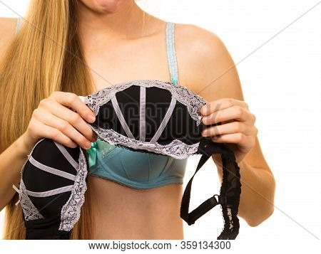 Young Blonde Woman Trying On Black Bra With White Lace. Bra Has Removed The Underwire. Bosom Concept