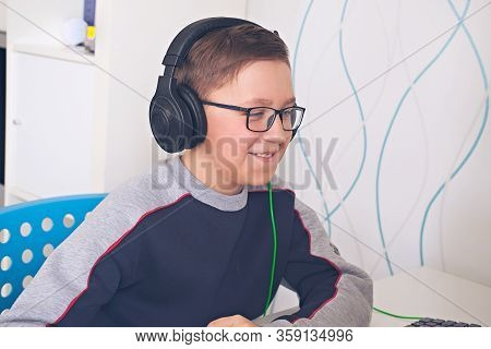 Teenager Boy In Glasses Looking At Computer Monitor. Distance Learning Concept. Boy In Earphones .