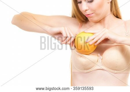 Young Woman Small Boobs Puts Big Fruit Grapefruit In Her Bra. Breast Enlargement Size Correction Con