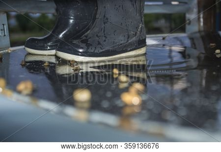 Blue Dark Child Rainboots In The Middle Of Pond Of Playground. Closeup