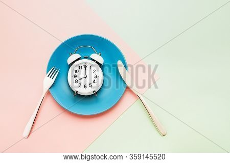 Intermittent Fasting Concept. White Alarm Clock On Empty Blue Dish With Knife And Fork On Pink-green