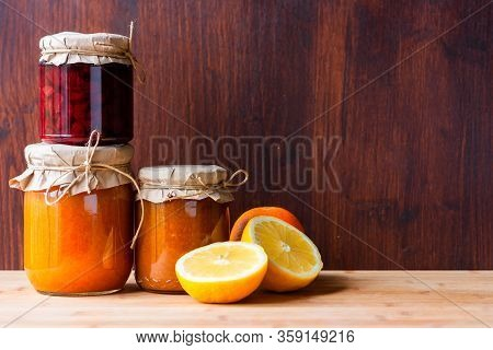 Jars With Various Jams And Lemon Cut And Orange On Dark Wooden Background. Strowberry And Apricot Ja