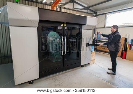 Worker Printmaker Technician Works On Large Modern 3D Printer Machine