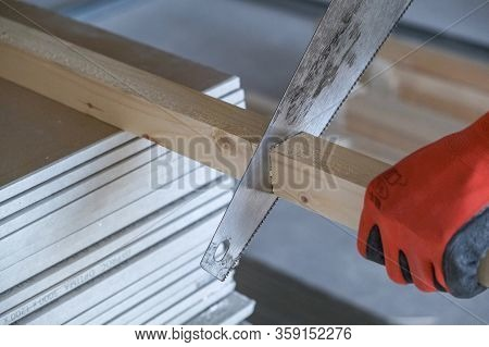 Worker Cuts Off A Wooden Block With A Hacksaw