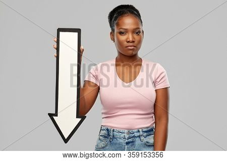 direction, failure and people concept - unhappy african american young woman holding big white thick downwards arrow over grey background
