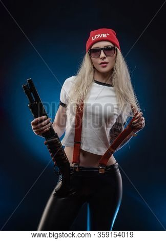 A Bright Blonde In A Red Hat With A Shotgun On A Dark Background