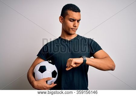 Handsome african american man playing footbal holding soccer ball over white background Checking the time on wrist watch, relaxed and confident