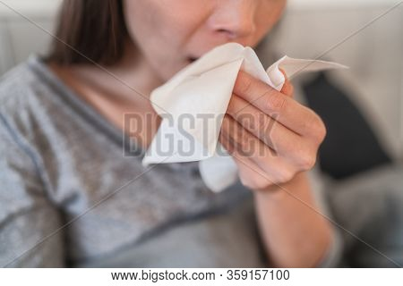 Cough in tissue covering nose and mouth when coughing as COVID-19 hygiene guidelines for coronavirus spread prevention.