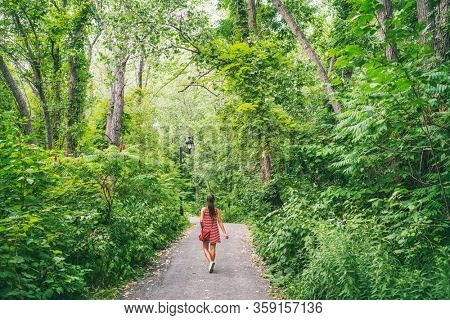 Outdoor summer walk in nature forest park girl enjoying outdoors freedom after self isolation quarantine from COVID-19 outbreak. Woman in red dress walking in woods trail path.