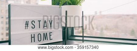 COVID-19 banner Coronavirus staying at home lightbox message sign with text hashtag #STAYHOME glowing in light to promote self isolation staying at home header background.