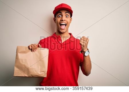 Young handsome african american delivery man holding paper bag with takeaway food screaming proud and celebrating victory and success very excited, cheering emotion