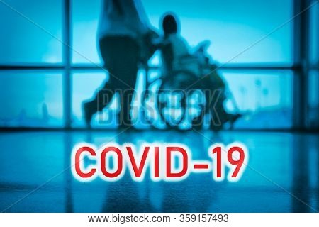 COVID-19 billboard red text on blue medical hospital background with doctor walking with disabled patient in wheelchair.