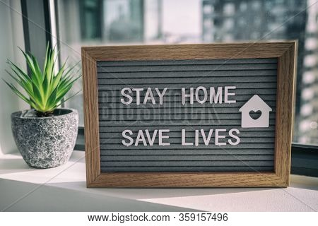 """STAY HOME SAVE LIVES"" staying home self quarantine COVID-19 Coronavirus text message sign for social distancing awareness. COVID-19 staying at home window background. Flatten the curve."