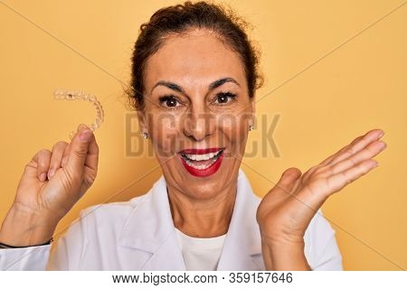Middle age senior dentist woman holding clear aligner for teeth correction very happy and excited, winner expression celebrating victory screaming with big smile and raised hands