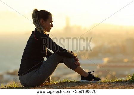 Runner Sitting In City Outskirts Contemplating Sunset